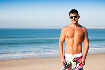 Handsome young muscular man at the beach