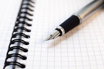 stylo plume posé sur un bloc de notes a spirales