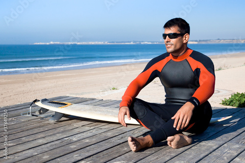 Surfer wearing a wetsuit with surf board.