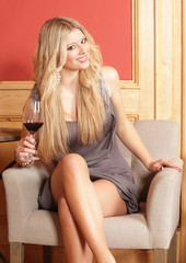 girl sitting on a chair with a glass of red wine