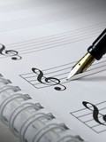 A fountain pen on blank sheet music. Selective focus