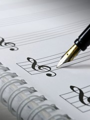 A fountain pen on blank sheet music. Selective focus