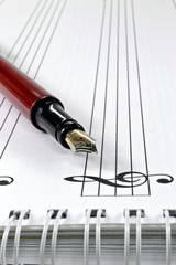 A fountain pen on a book of blank sheet music
