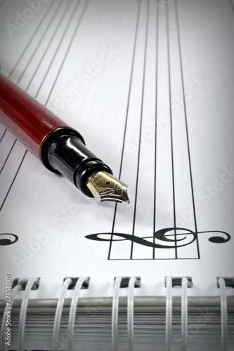 A fountain pen on a blank book of sheet music