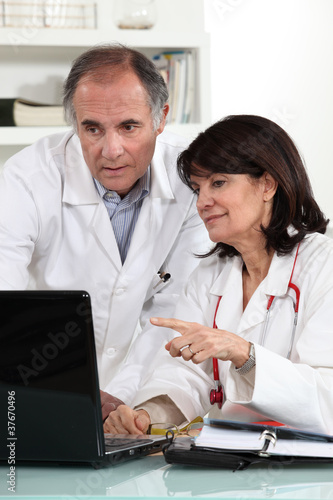 Doctors looking at a computer and sharing their opinions