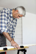 Elderly handyman preparing plank of wood to be cut