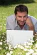 Man on laptop in field