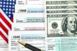 Tax forms with pen, money and U.S. flag.