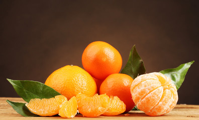 tangerines with leaves on wooden table on brown background