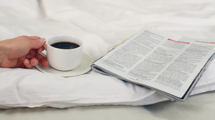Woman drinking coffee in bed and reading magazine