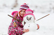 girl with her snowman winter fun