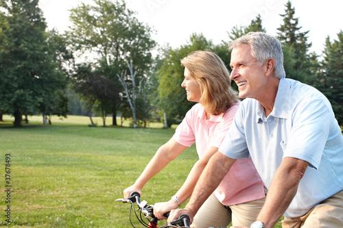 Aluminium Wielersport Senior couple cycling in park.