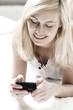 lächelnde Frau tippt eine SMS in Smartphone