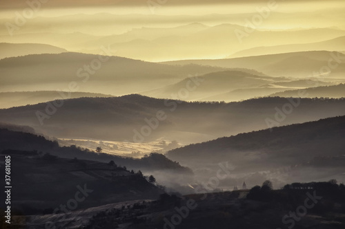 valley in a beautiful early morning with fog and hills