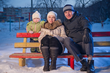 Happy family with adorable baby sit on bench on playground