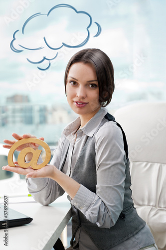Portrait of a cheerful Business woman sitting on her desk holdin