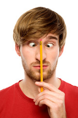Man holding pencil between his eyes