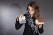 Junge Frau zeigt Taschenrechner mit Haus, Blick skeptisch