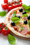 Pizza with ham and black olives