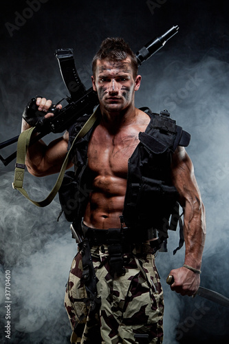 Muscular young sexy naked soldiers with weapons in a flak jacket