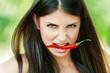 girl with chili pepper in teeth