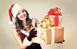 Beautiful woman in a red dress and hat of Santa with a big gift