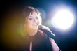 singer with a microphone singing a song.woman on a black backgro