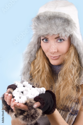 Woman in winter hat and gloves with snow