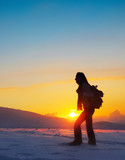 Woman traveler hiking in winter mountains