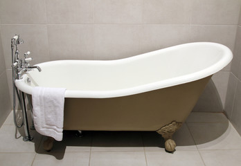Old style bath tub with metal legs and towel, vintage style