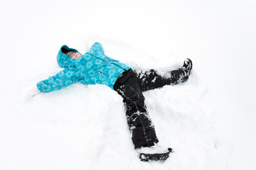 Boy in blue jacket lying in the snow