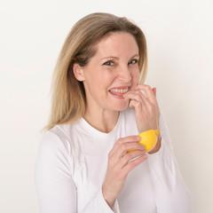 Frau probiert eine Zitrone