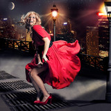 Fototapety Red dressed Marilyn Monroe double with flying skirt in the city