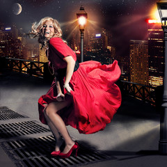 Red dressed Marilyn Monroe double with flying skirt in the city