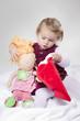 kleines Mädchen zieht Puppe eine Nikolaus Mütze an