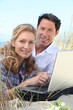 Couple smiling on laptop.