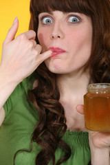 Woman dipping little finger in jar of honey