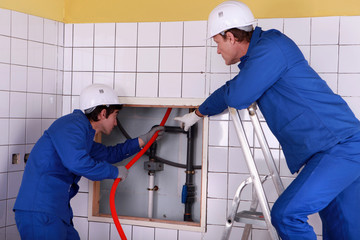 Two plumber working in public rest room