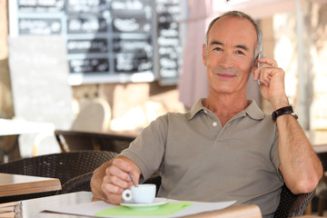 Senior man on phone drinking a coffee