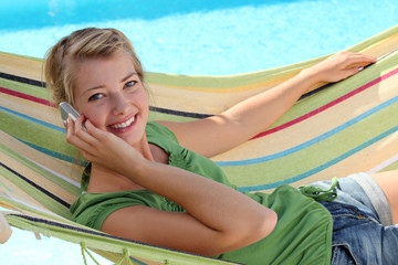 Blond woman with mobile telephone laying in hammock
