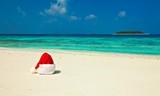 Fototapety Santa hat is on a beach