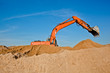 Excavator at a sandpit with raised bucket over sky