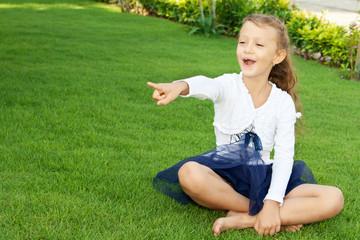 Девочка на зеленом газоне показывает пальцем вперед
