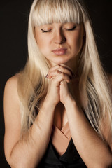 Young blond beautiful woman praying
