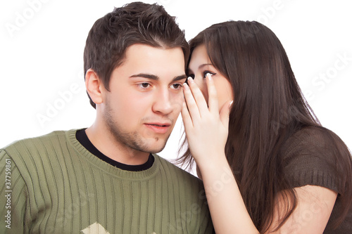 Portrait of young woman telling a secret to a man over a white b