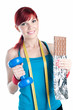 Sportive red-haired woman with dumbbell and a bar of chocolate