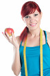 Sportive young woman with an apple and a centimeter