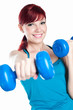 Studio shot of smiling young woman exercising with dumbbells