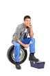 A thoughtfull mechanic sitting on a spare tire and holding a wre