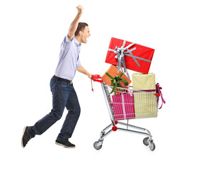 Euphoric male pushing a shopping cart full with gifts